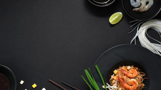 パッドタイのヘッドショット、エビ、卵、黒いテーブルの上の黒いセラミックプレートの成分とタイ麺のフライをかき混ぜる Premium写真