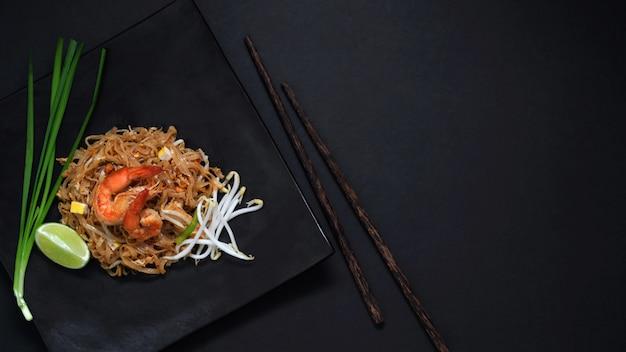 パッドタイのトップビュー、黒いテーブルの上の黒いセラミックプレートにエビと卵とタイ麺の炒め Premium写真