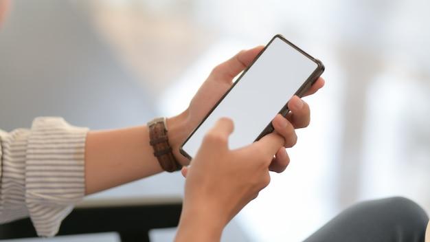 Крупным планом зрения бизнесмена текстовых сообщений на смартфоне, сидя на диване Premium Фотографии