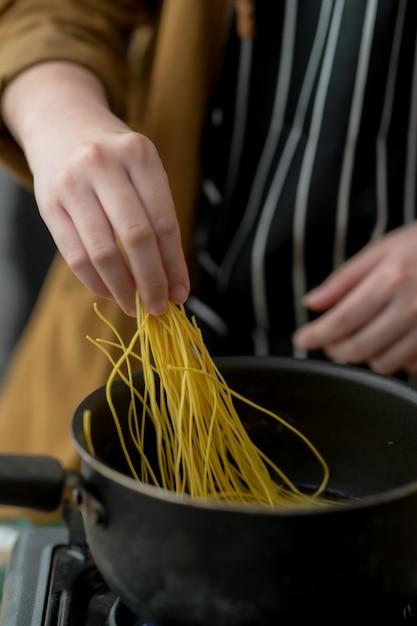 麺メニューの食材を準備する若い女性のショットをトリミング Premium写真