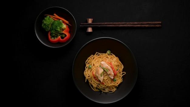 シェズワンヌードルまたはチャウメンの野菜、チキン、チリソース添えのトップビュー Premium写真