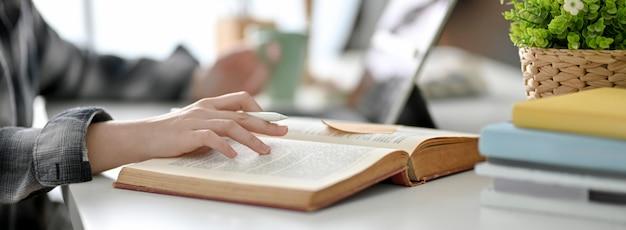 彼女の今後の試験に備えるために本を読んでいる大学生の側面図 Premium写真