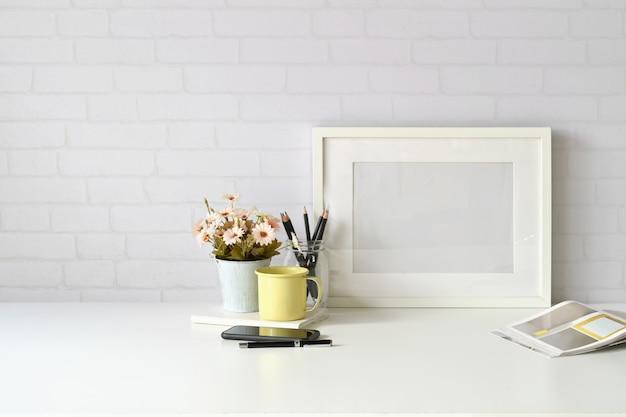 職場とコピースペース、モックアップポスター、コーヒーマグと花植物のあるスタイリッシュなワークスペース。 Premium写真