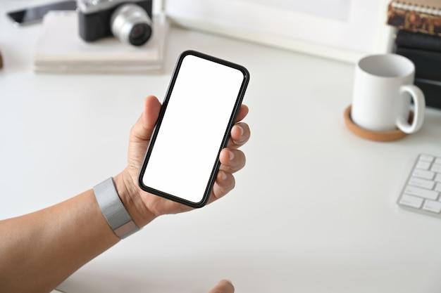 デスクワークで人間の手でモバイルのスマートフォン。 Premium写真