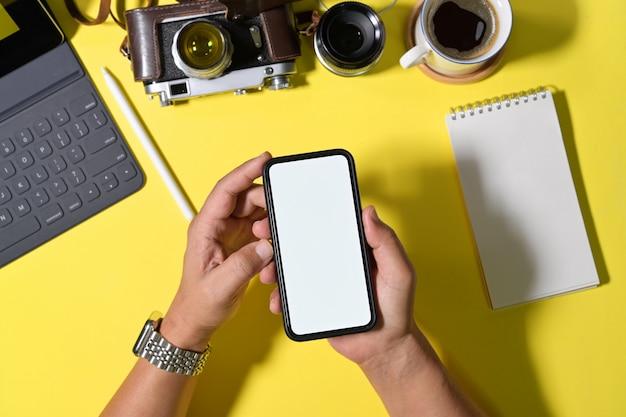 男の空白の画面携帯電話を手にワークスペース Premium写真