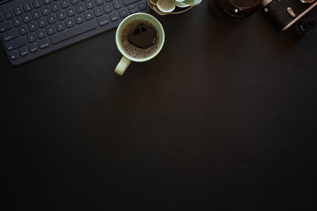 キーボードタブレットとビンテージカメラとダークレザーオフィス写真デスクテーブル Premium写真