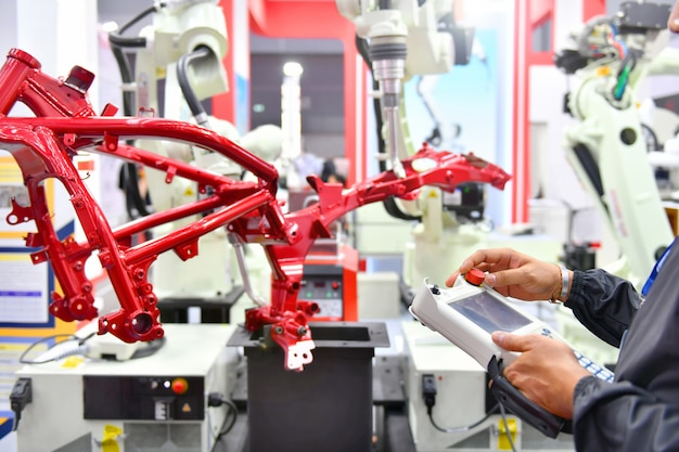 エンジニアのチェックと制御の自動化オートバイ用ロボットアームマシンオートバイプロセスの工場での構造。 Premium写真