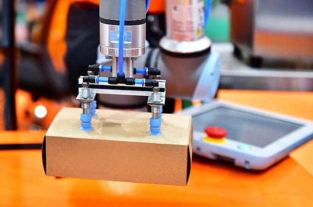 ロボットアームは、生産ライン工場の自動産業機械装置に製品ボックスを配置 Premium写真
