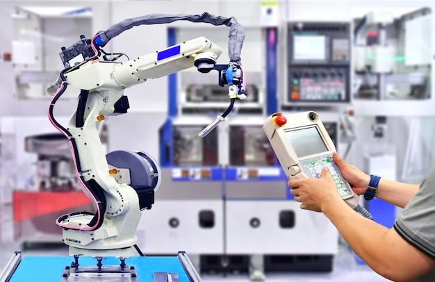 オレンジ色の近代的なロボットシステム工場、産業用ロボットのエンジニアチェックおよび制御自動化。 Premium写真