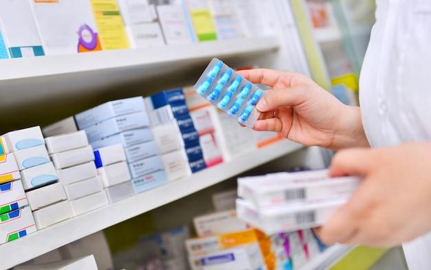 Фармацевт, держащий коробку с лекарством и капсулу в аптечной аптеке. Premium Фотографии