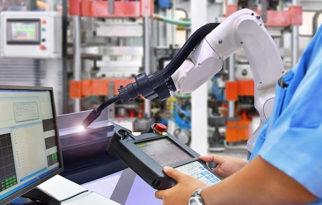 エンジニアが工業用の白いロボットアームを溶接する最新の高品質自動化を制御する Premium写真