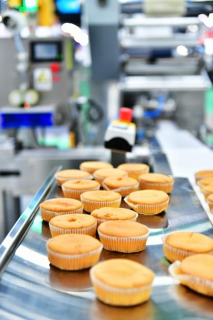 工場のコンベアベルト装置機械、工業用食品生産の自動ベーカリーマフィン生産ライン。 Premium写真