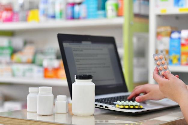 Аптекарь используя компьтер-книжку компьютера в аптеке аптеки или аптеки. рука пакет медицины и ключ рецепт заказа. Premium Фотографии
