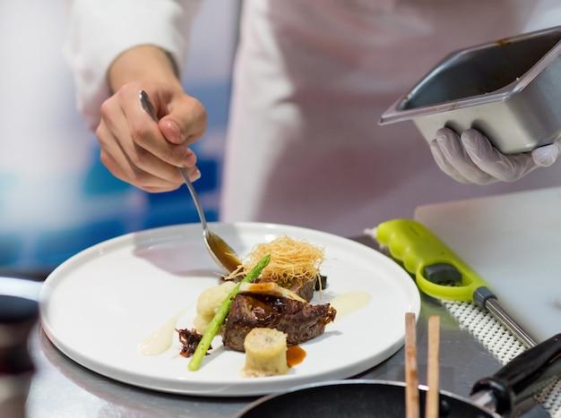 シェフが台所で料理を作る、シェフが料理を作る Premium写真