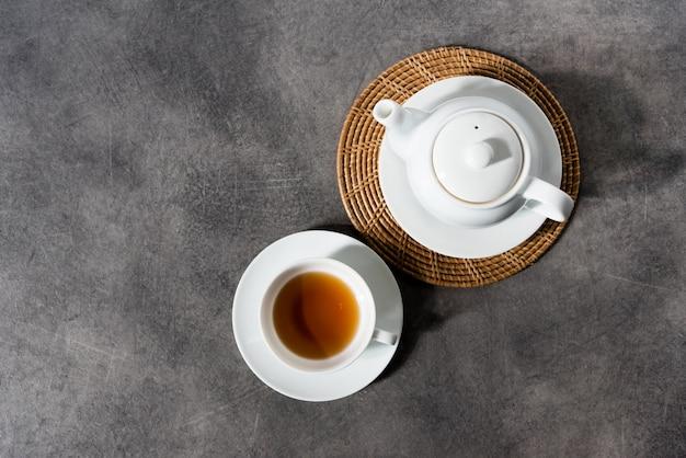 Белая фарфоровая чайная чашка и чайник, английский чай на столе, послеобеденный чай Premium Фотографии