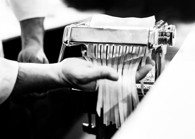 Шеф-повар делает макароны с машиной, свежие макароны домашнего приготовления Premium Фотографии