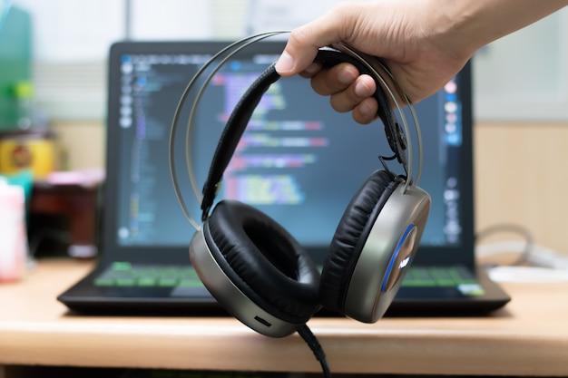 ノートパソコンの背景にヘッドフォンを持っている手。 Premium写真