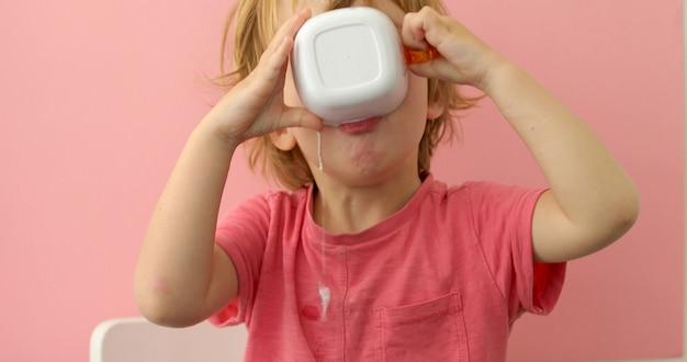 幸せな子供はカップからミルクを飲む Premium写真