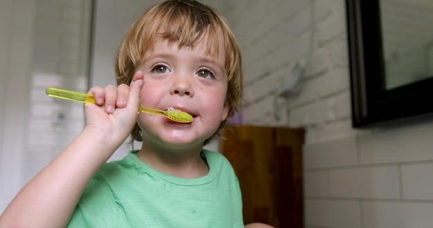 家庭のお風呂で歯を磨くことを学ぶ小さな金髪の少年。 Premium写真
