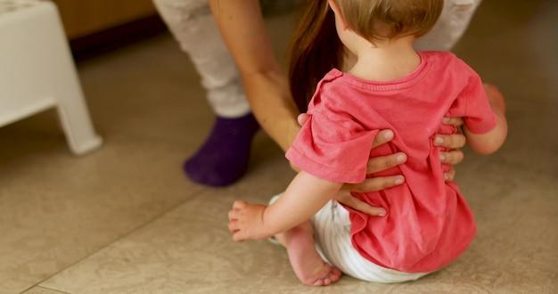 女性が床から子供を拾う Premium写真