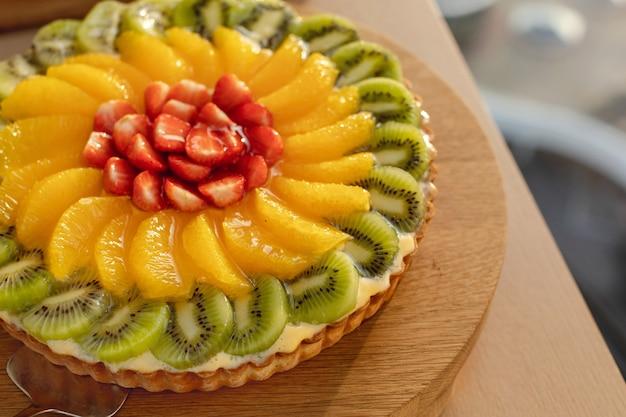 Красочный украшенный фруктовый торт на деревянной тарелке Premium Фотографии