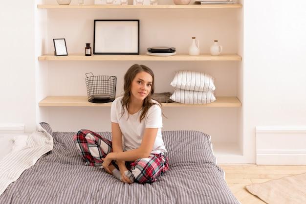 Элегантная женщина в домашней одежде, отдыхая на кровати Premium Фотографии