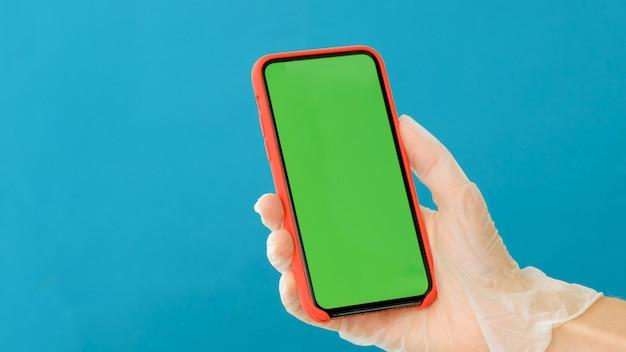 Рука в резиновой перчатке держит смартфон с зеленым экраном Premium Фотографии