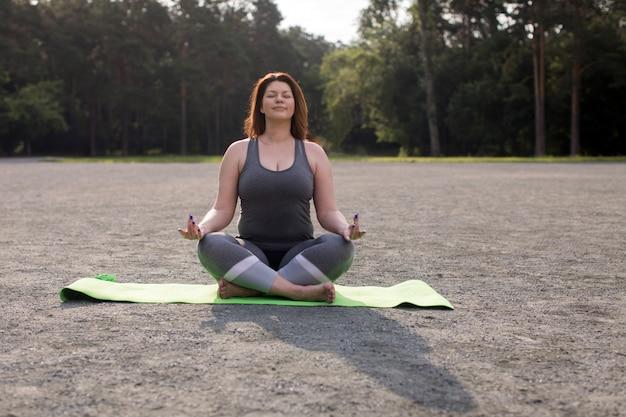 屋外のヨガを瞑想プラスサイズの女の子 Premium写真