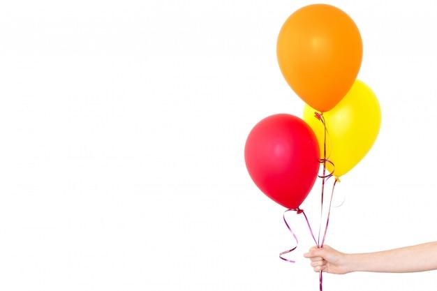 女の子の手は、白い背景で風船を保持しています Premium写真