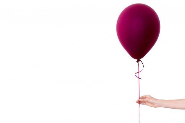 Женщины рука держит пурпурный воздушный шар белый фон Premium Фотографии