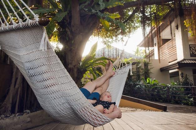 ハンモックで眠っている男の子と男 Premium写真