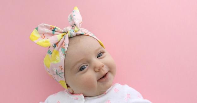 生まれたばかりの赤ちゃん女の子ピンクの背景を笑顔 Premium写真