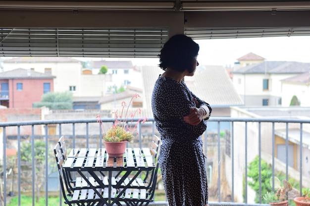 Грустная женщина смотрит в окно дома Premium Фотографии