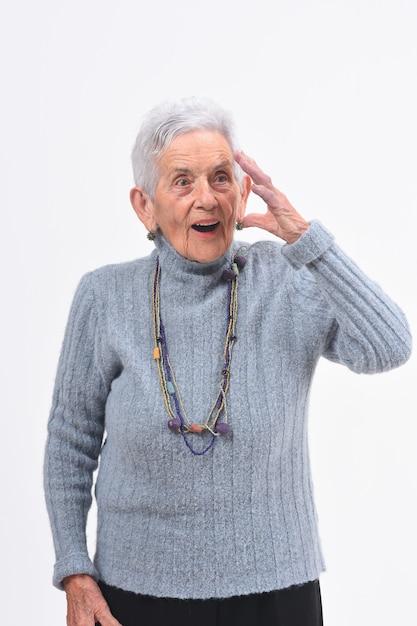 物忘れや白い背景の上の驚きの表現を持つ年配の女性 Premium写真