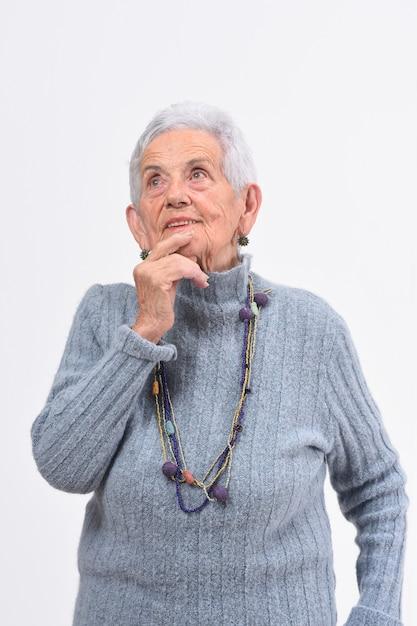 Старшая женщина имея сомнение или вопрос на белой предпосылке Premium Фотографии