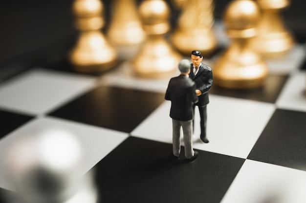 ミニチュアビジネスパートナーシップハンドシェイクコンセプト。金と銀のチェスの取引後の成功したビジネスマンハンドシェイク Premium写真