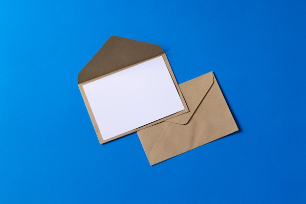 空白の白いカードを持つモックアップ茶色クラフト封筒文書 Premium写真