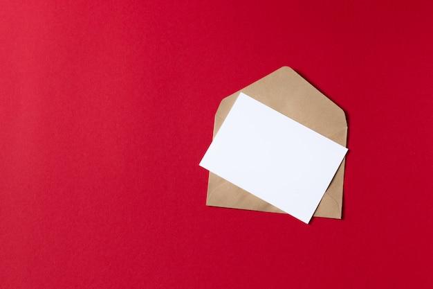 クラフト茶色の紙封筒テンプレートモックアップで空白の白いカード Premium写真