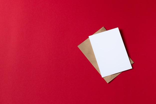赤の背景にモックアップのクラフト茶色の紙封筒テンプレートカード Premium写真