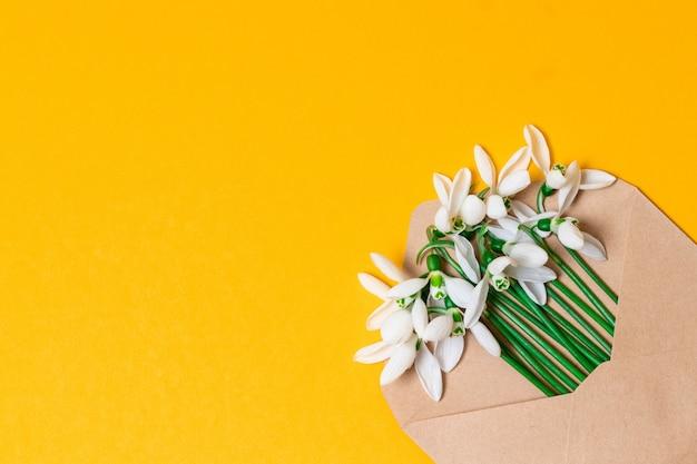 Конверт ручной работы с весенней цветочной композицией. вид сверху. плоская планировка, вид сверху пригласительный билет. Premium Фотографии