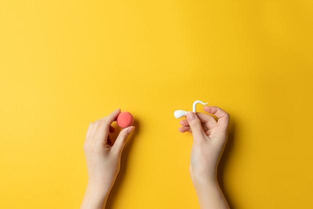 黄色の背景に女性の卵の受精。コピースペース Premium写真