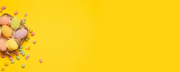 イースター。黄色の背景に色の装飾と枝編み細工品バスケットのカラフルな卵 Premium写真