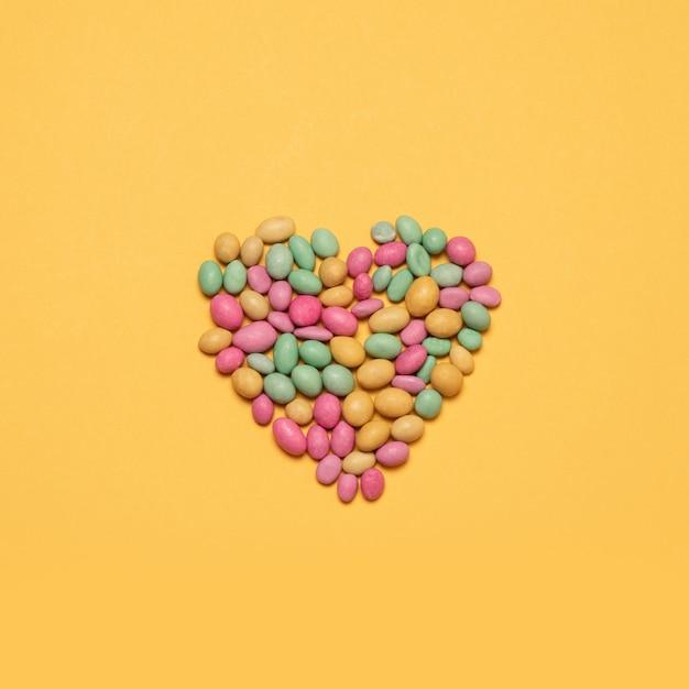 色とりどりのハート形の黄色の背景にキャンディー Premium写真