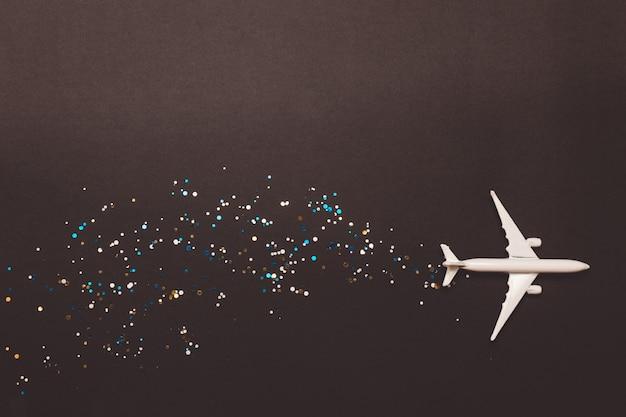 黄色の背景に輝くミニチュアおもちゃの飛行機。旅 Premium写真