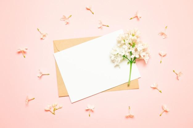 モックアップホワイトグリーティングカードと明るい背景にライラックの枝を持つ封筒 Premium写真