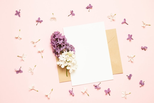 Макет белая открытка и конверт с ветвями сирени на светлом фоне Premium Фотографии