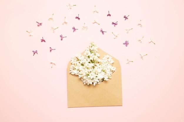 Макет конверта с ветвями сирени на розовом фоне Premium Фотографии