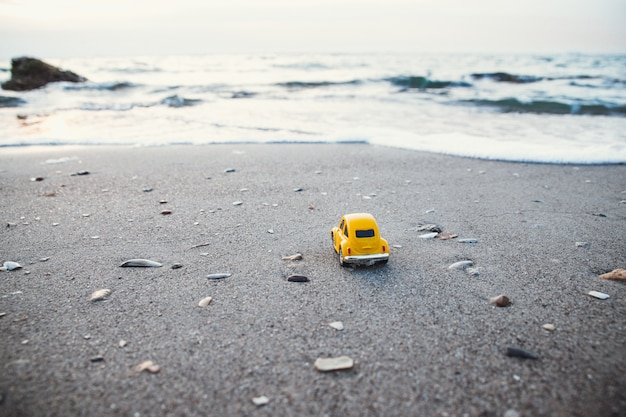 休暇や旅行のコンセプトです。夏の日差しの中でビーチで黄色のおもちゃの車 Premium写真