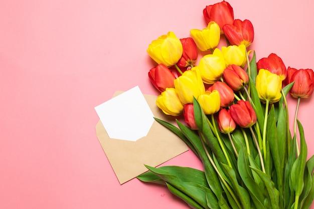 Минималистичный макет карты с красными тюльпанами, цветком, ремесленным конвертом Premium Фотографии