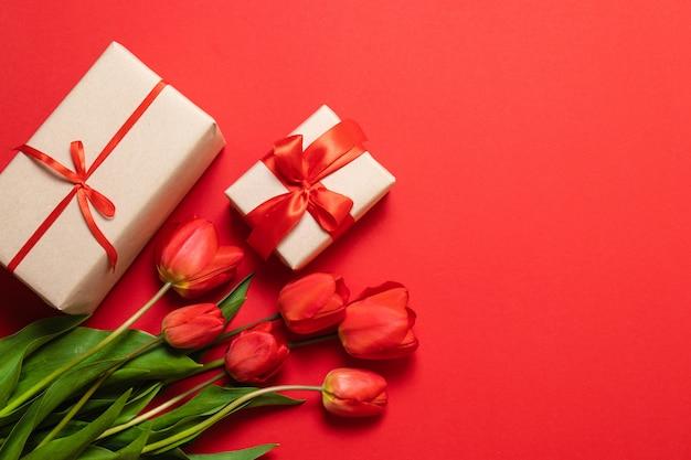 春の組成赤いチューリップと赤い背景の上のギフトボックスの花束。 Premium写真